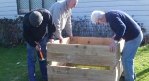 Three men assembling compost bin from fence paling